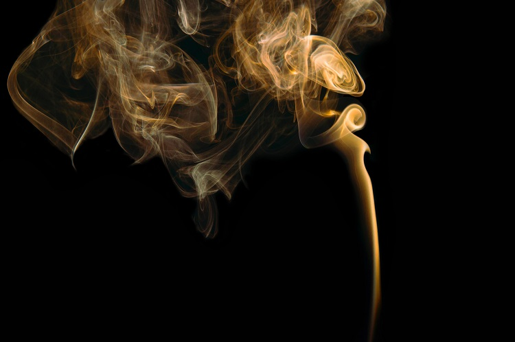 An orange-tinged stream of cigarette smoke against a black background