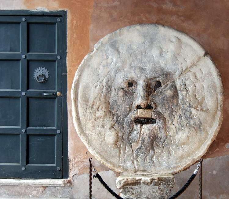 The Mouth of Truth sculpture on the wall of a Roman building