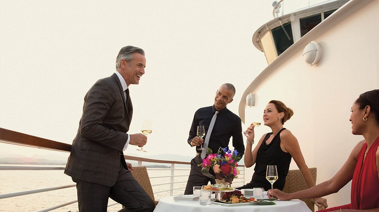 Friends drinking wine on their balcony on a Seabourn cruise