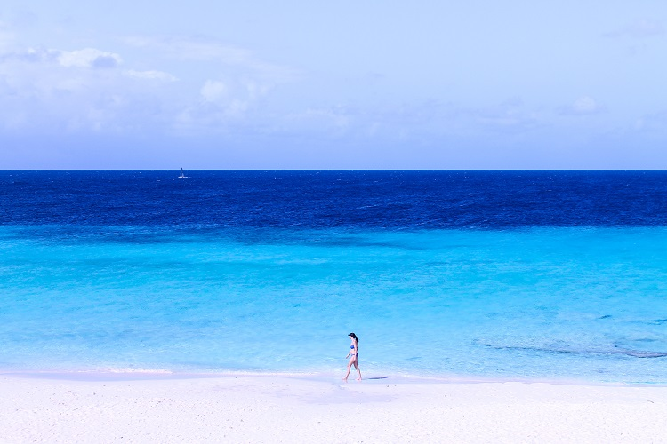 Woman walking down a secluded Caribbean beach in front of bright blue sea