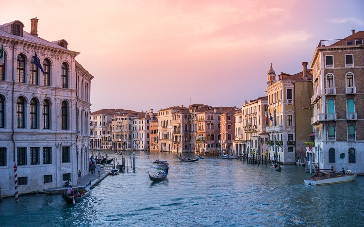 A gondola making its way down a canal in Venice at sunset