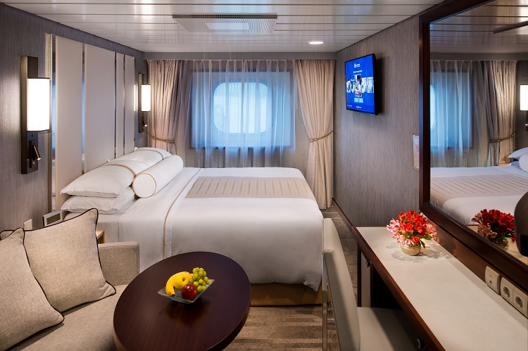 Elegant interior of an Oceanview stateroom with a fruit bowl and sofa