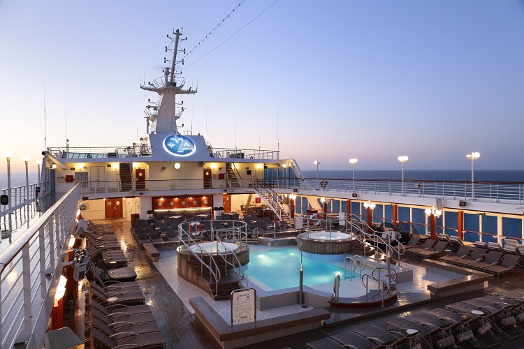 The pool deck on-board Azmara Journey lit up at sunrise