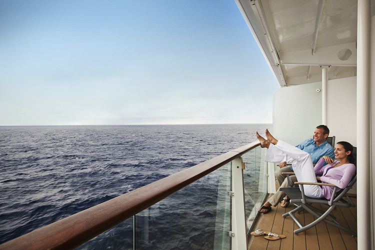 A couple enjoying the view from their balcony on-board Celebrity Eclipse