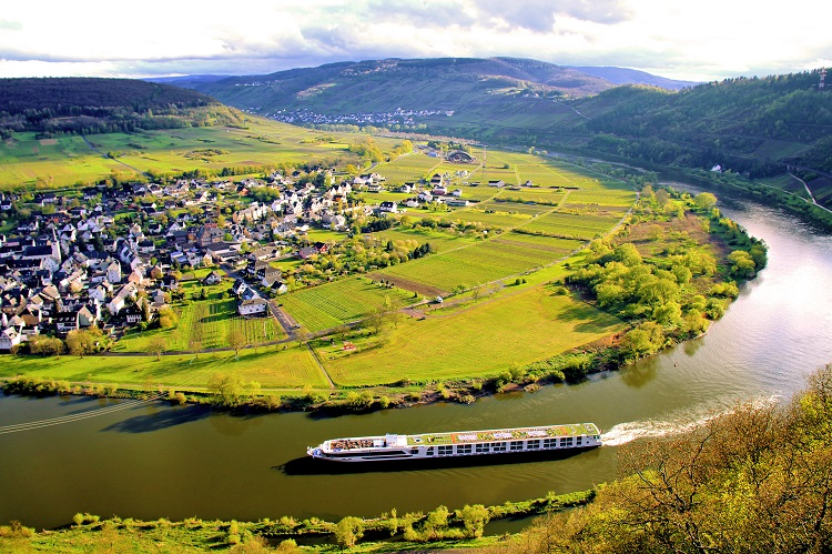 A Crystal river cruise ship sailing along a scenic river in Europe