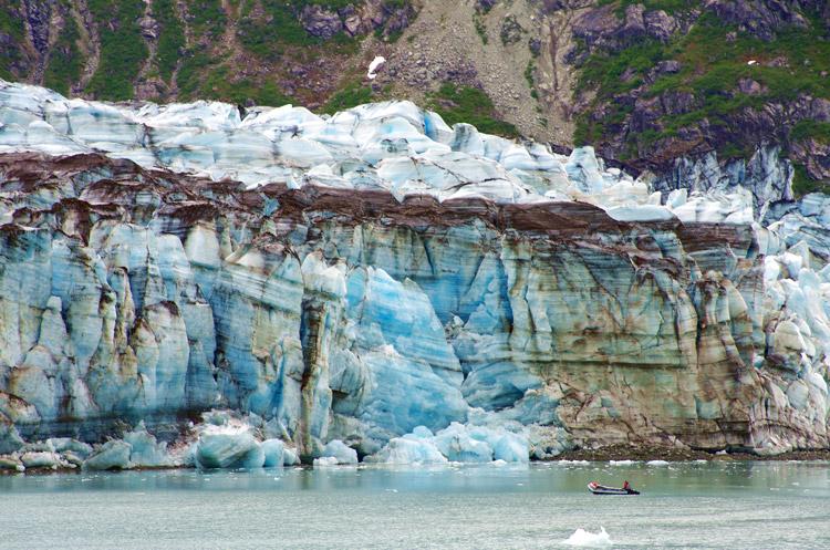Tiny excursion boat sailing towards a glacier in Glacier Bay National Park