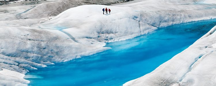 Figures walking by a bright blue melt pool on a glacier in Juneau