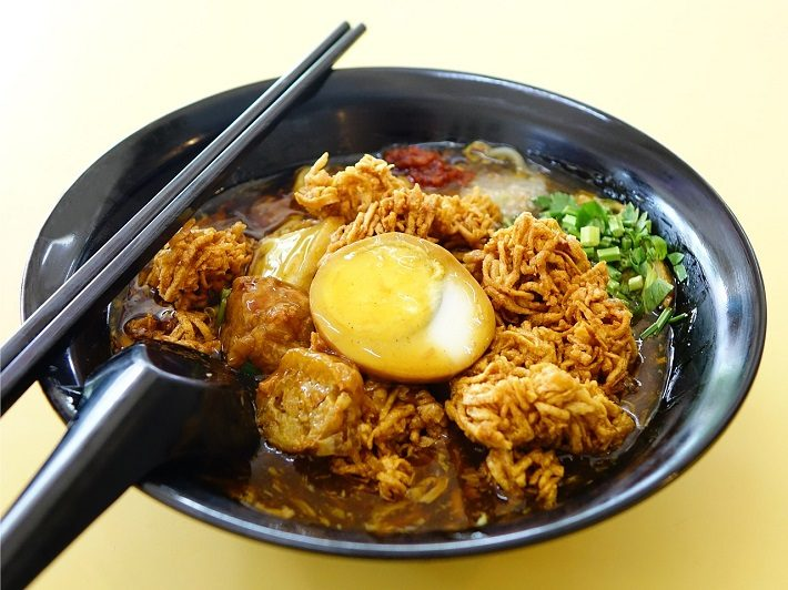 A bowl of lor mee with chopsticks on a table in Singapore