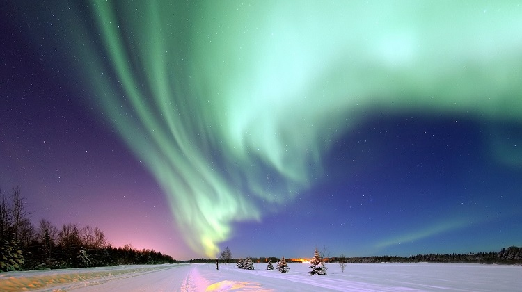 Green aurora borealis shining a snow-covered field in Alaska