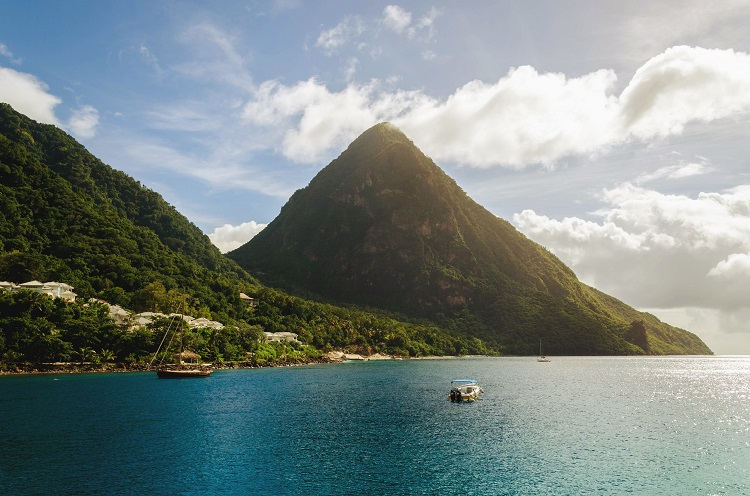 A lush mountain rising up out of the bright blue sea in St Lucia