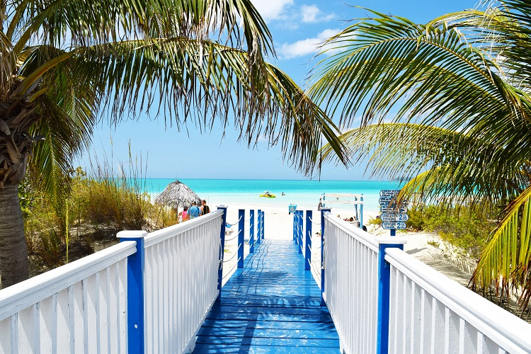 Blue and white wooden walkway leading down to a bright white beach in Cuba