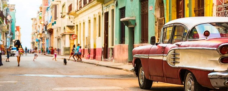 Pink and white classic car parked on a bright Cuban street