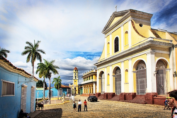 Tourists admiring a stunning yellow colonial building in Trinidad
