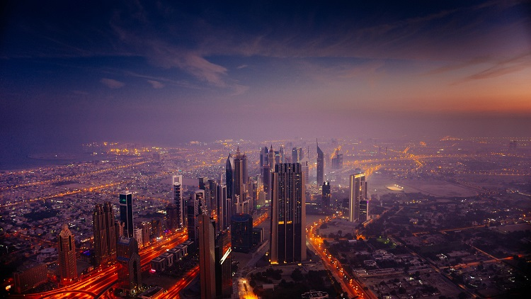 Dubai illuminated at night as the sun sets and bathes the city in purple light