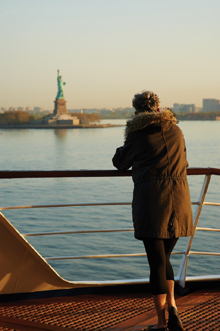 A cruise passenger admiring the view of the Statue of Liberty from the deck of a New York cruise ship
