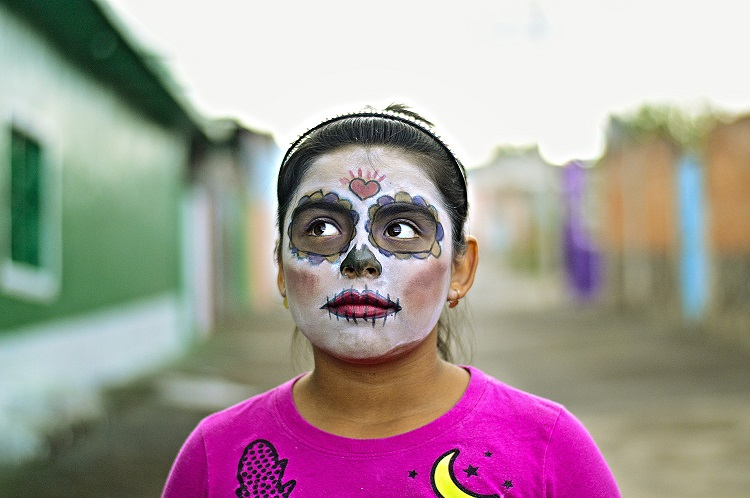 A child standing in a street in Mexico wearing Day of the Dead makeup