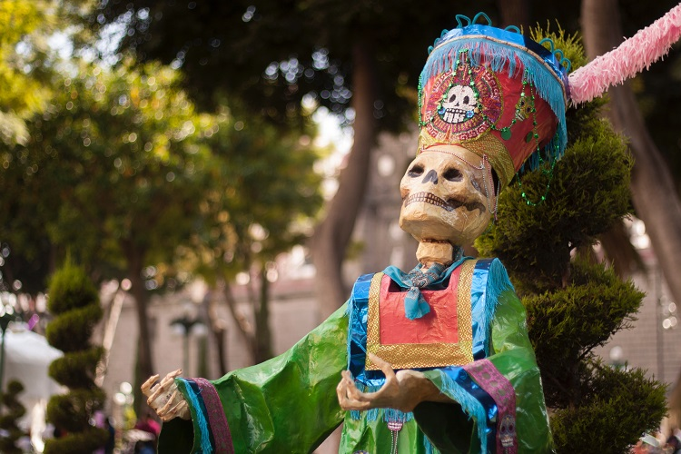 A skeleton figure dressed in traditional clothing during a Day of the Dead parade