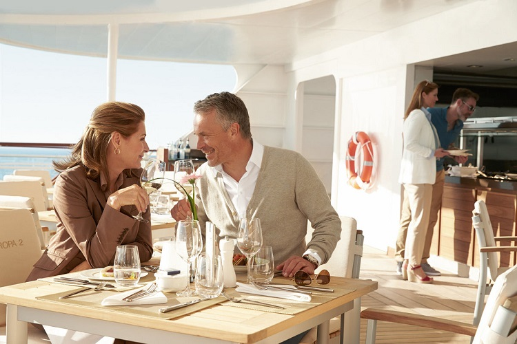 A couple sharing wine and dining alfresco on-board Hapag-Lloyd's MS Europa 2