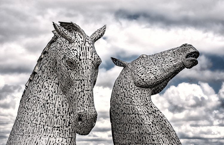 Two huge horse head statues looming up against a cloudy sky in Scotland