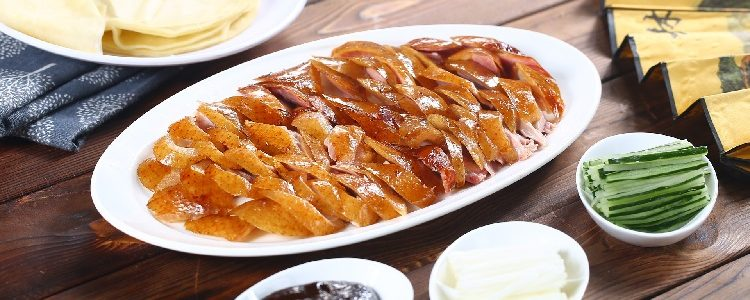 A plate of Peking duck surrounded by toppings and pancakes
