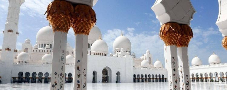 Ornate pillars and bright white exterior of the Sheikh Zayed mosque in Abu Dhabi