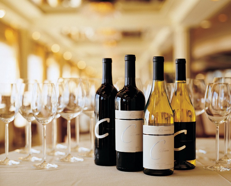 Bottles of red and white wine on a table with wine glasses on a Crystal cruise ship