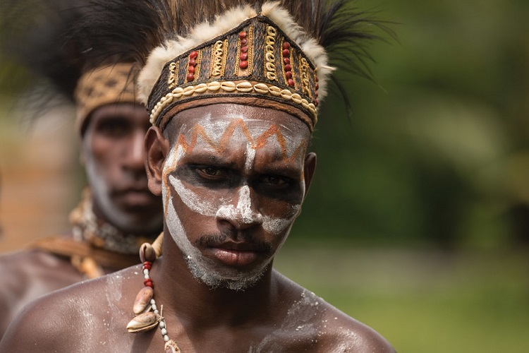 Local villagers in Papua New Guinea wearing ceremonial dress and face paint