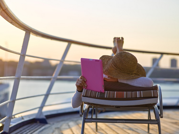 Woman reading a book on an iPad as she sunbathes on the deck of a Silversea cruise ship