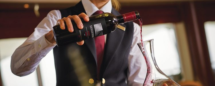 A sommelier pouring red wine into a decanter on-board a Silversea cruise ship