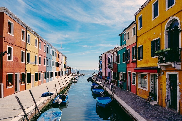 Colourful buildings lining a Venetian canal leading down to the ocean