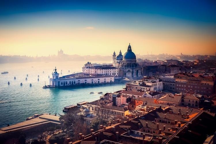 The Venetian skyline bathed in orange light as the sun sets