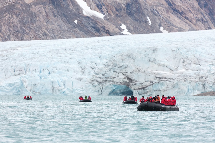 Expedition cruise guests driving away from a glacier in Zodiacs