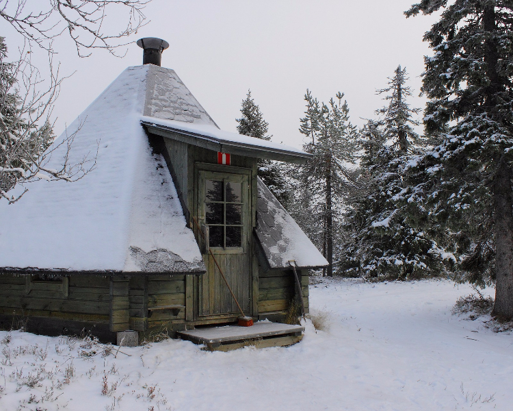 A quaint cabin covered in snow in Lapland