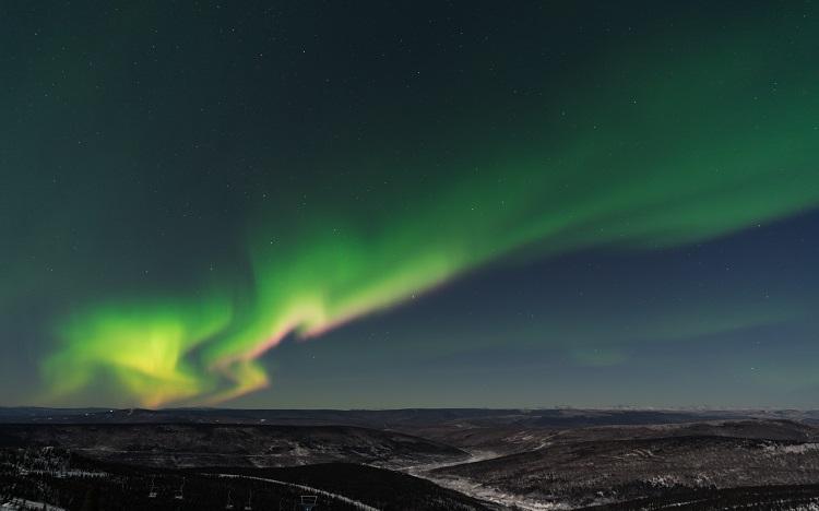 Green Northern Lights dancing over the snow in Fairbanks in Alaska
