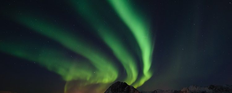 The Northern Lights in streams over the snow and mountains in Lofoten in Norway