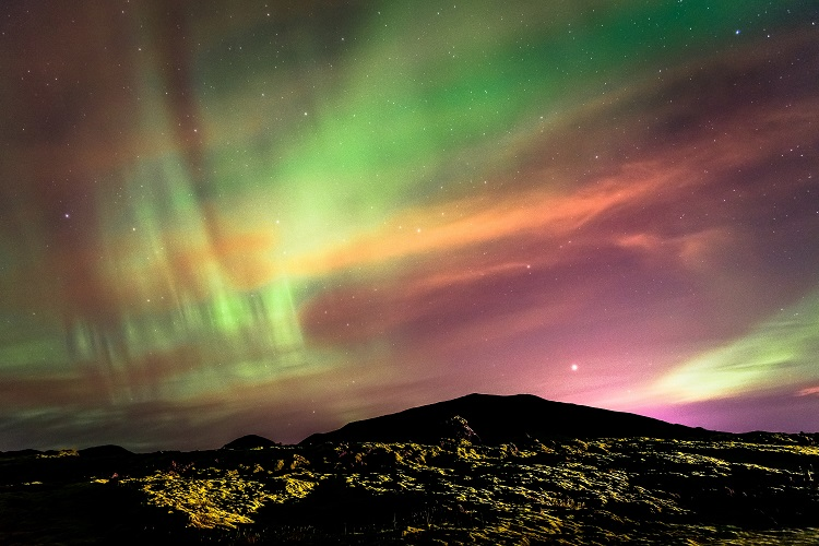 Green and purple Northern Lights over the lava fields outside Reykjavik in Iceland