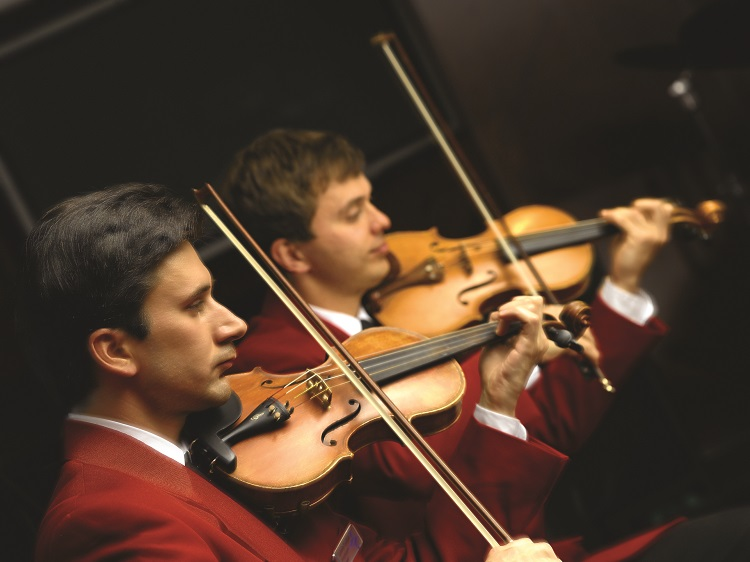 Violinists playing in an orchestra on-board an Oceania Cruises ship