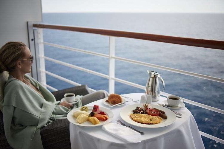A Penthouse Suite guest enjoying al-fresco breakfast on her balcony