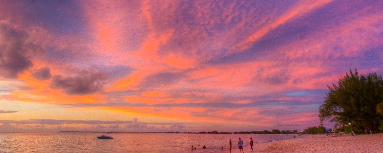 Seven Mile Beach in Grand Cayman bathed in pink light at sunset