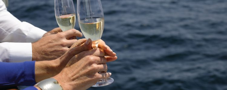 Silversea passengers holding glasses of wine as they look out over the side of their cruise ship