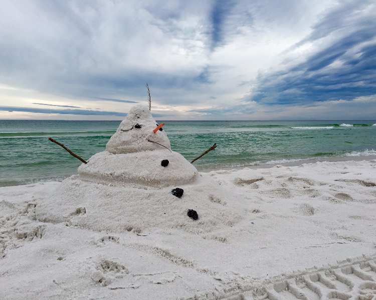 A snowman made out of sand on a beach in the Caribbean