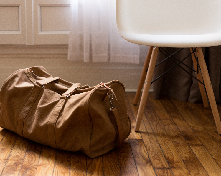 Brown luggage bag waiting to be collected with Regent's personal door-to-door service