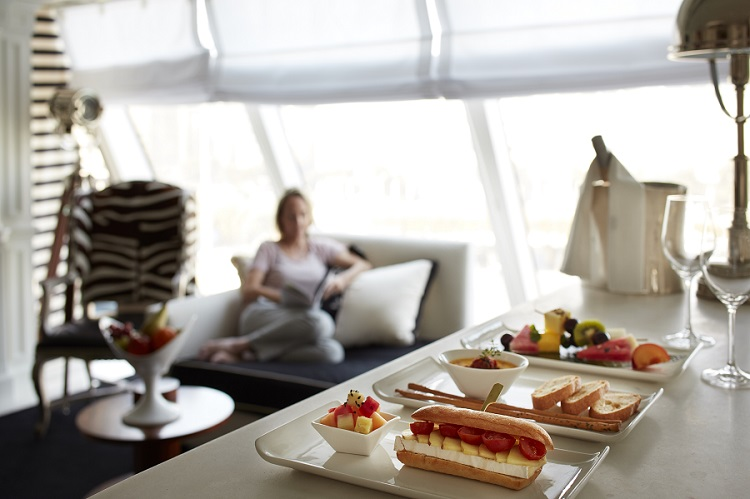 A guest being served room service in an Owner's Suite on-board Oceania Riviera