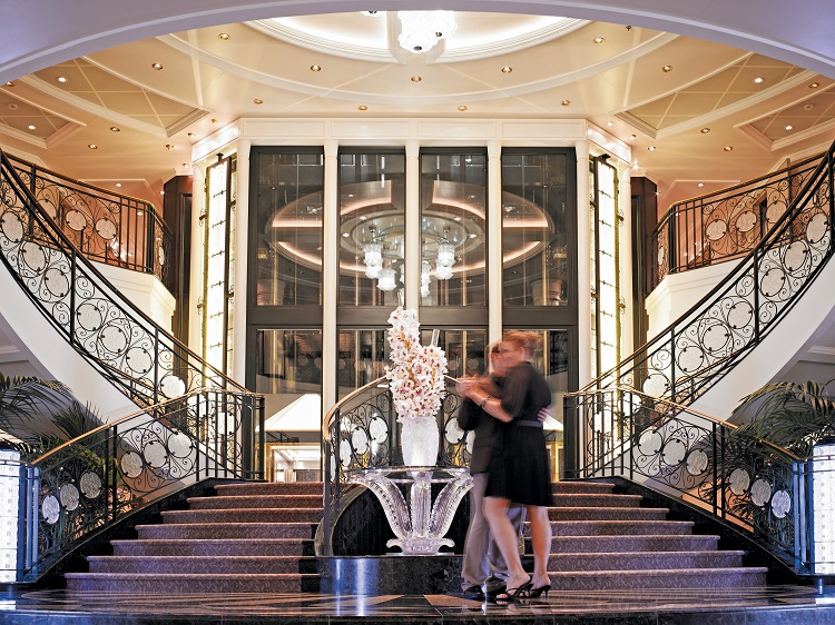 A couple dancing in front of the grand staircase on-board Oceania Riviera