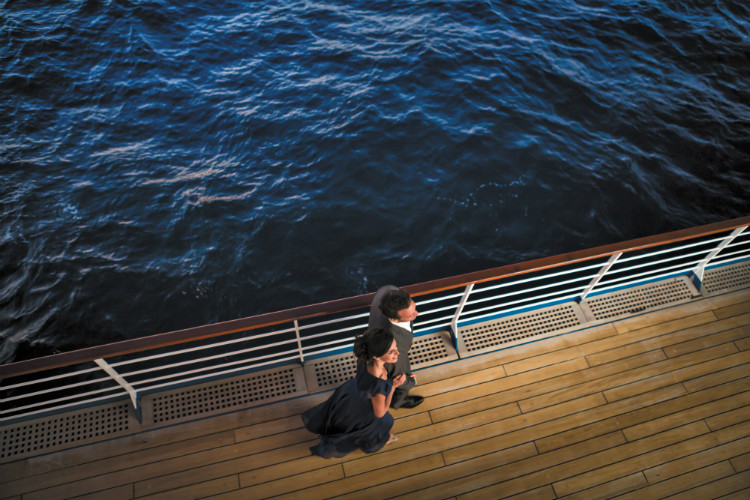 A couple strolling along deck in the evening on-board Regent Seven Seas Voyager
