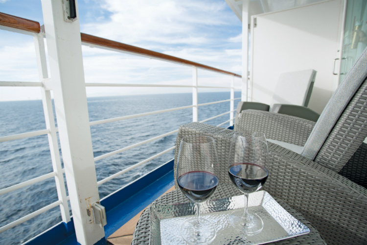 Glasses of red wine on the balcony of a Seven Seas Voyager Deluxe Veranda Suite