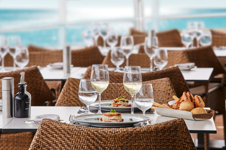 Glasses of wine on tables at the elegant Pool Grill on-board Silver Muse