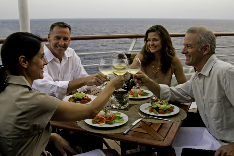 Friends dining on their balcony on an Azamara cruise ship