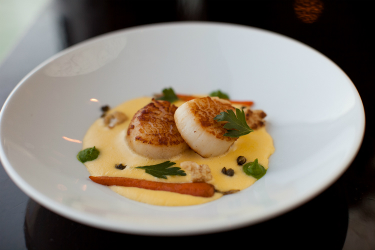 A bowl of scallops and sauce in the Prime C restaurant on an Azamara cruise