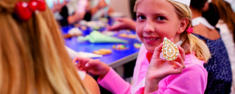 Children taking part in a cookie baking class on a Crystal Cruises ship